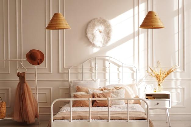 Witte scandinavische slaapkamer in de zon. beige accessoires. foto van het interieur vanuit de fotostudio