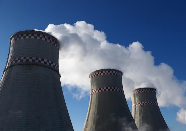 Witte schadelijke smog in blauwe lucht die uit industriële pijpen verdampt