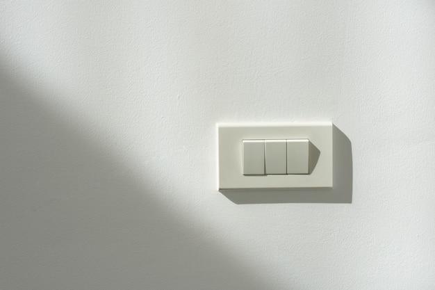 Witte schakelstroom op een witte muur met licht- en schaduwcontrast.