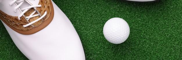 Witte schoenen en bal die op groene golfbaanclose-up liggen