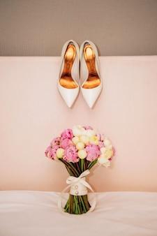 Witte schoenen en een boeket. bruiloft boeket met witte en roze pioenrozen.