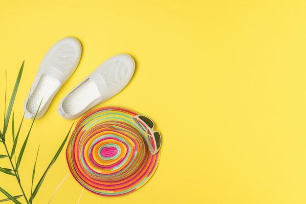 Witte schoenen, hoed en bril op een felgele achtergrond. het concept van zomervakantie en reizen.