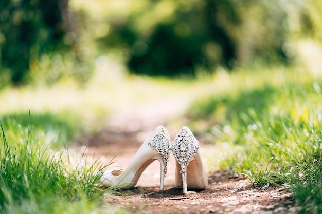 Witte schoenen met een achtergrond versierd met stenen op een achtergrond van groen gras met een ondiepe scherptediepte.
