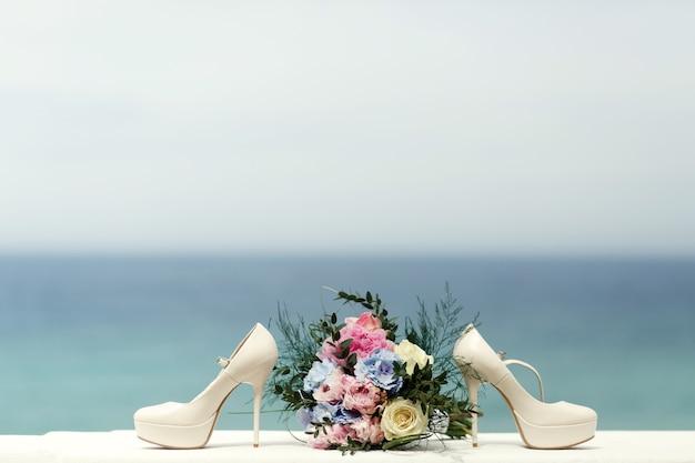 Witte schoenen staan aan de andere kant van het bruidsboeket
