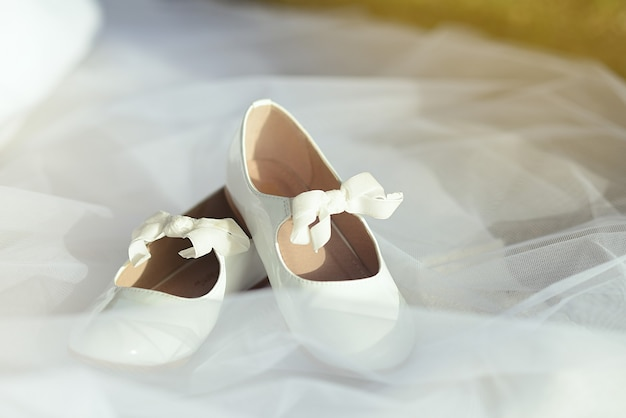 Witte schoenen voor eerste communie meisje over jurk