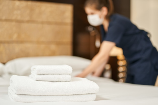Witte schone handdoeken op het bed met een meid in een masker op de achtergrond. hotelserviceconcept