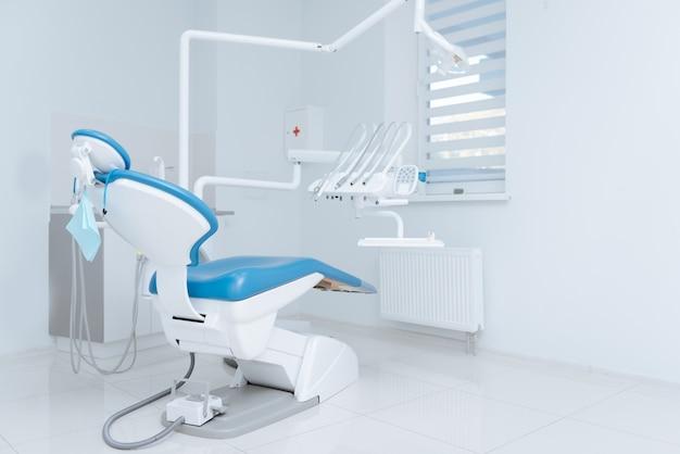 Witte, schone, mooie stoel en uitrusting die midden in een goed verlichte kamer staan en wachten op een nieuwe dag om te beginnen