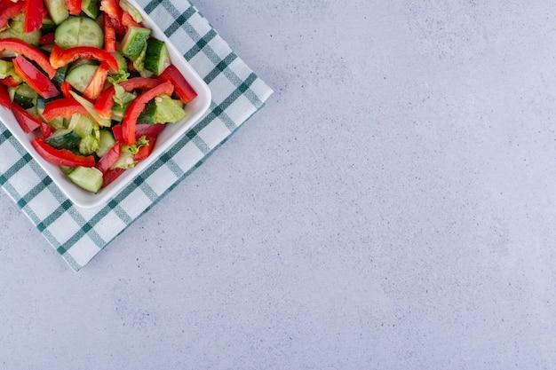Witte schotel van gemengde groentesalade op een verteld tafelkleed op marmeren achtergrond. hoge kwaliteit foto