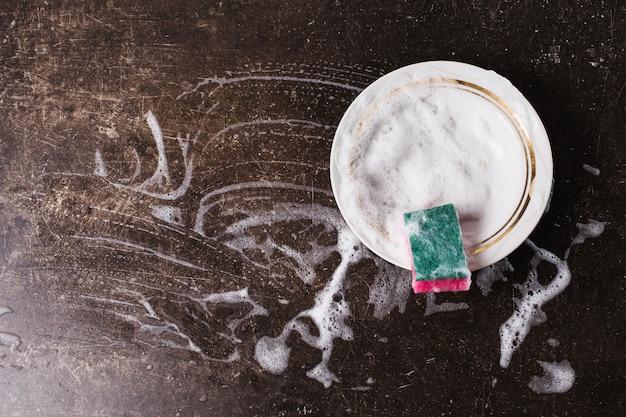 Witte schotel, wasmiddel en spons voor gerechten op een donkere marmeren achtergrond. hygiëne. doe de afwas
