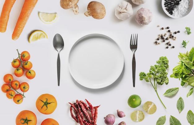 Witte schotelrand met biologische groenten, kruiden en specerijen, op witte achtergrond