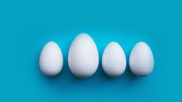 Witte schuim eieren op blauwe achtergrond. plat lag, bovenaanzicht. pasen-concept.