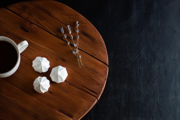 Witte schuimgebakjes en mok warme koffie op een rustieke houten tafel.
