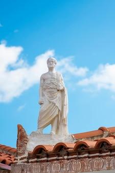 Witte sculptuur gemaakt van steen in oude griekse stijl, een man gelegen aan de rand van een dak van een gebouw in griekenland