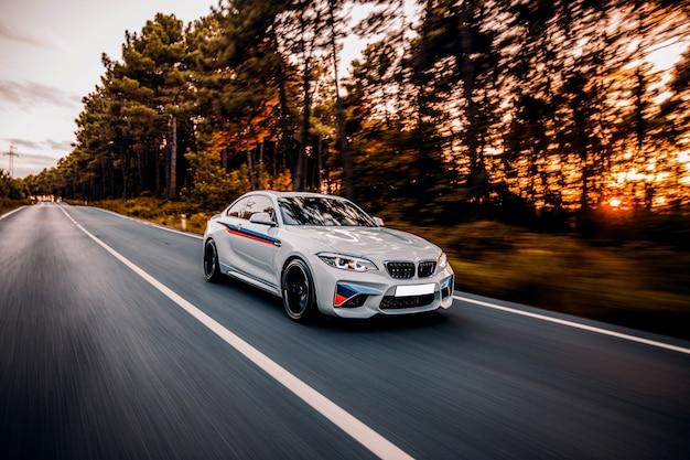 Witte sedan rijden op de snelweg dwars door het bos