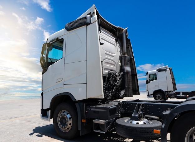 Witte semi vrachtwagens parkeren op een blauwe hemel