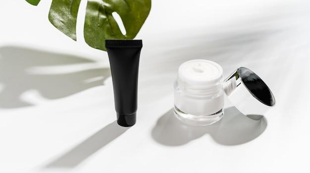Witte serumfles en zalfpotje, model van schoonheidsproductmerk.