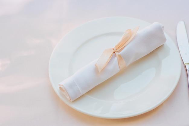 Witte servet op het bord op tafel bestek eten lunch feestconcept