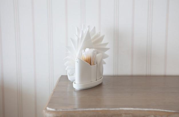 Witte servetten in houders op houten tafel