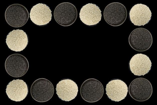 Witte sesam, zwarte sesamzaden op een zwarte bowlon zwarte achtergrond