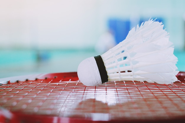 Witte shuttle en badmintonracket rood in badmintonveld.