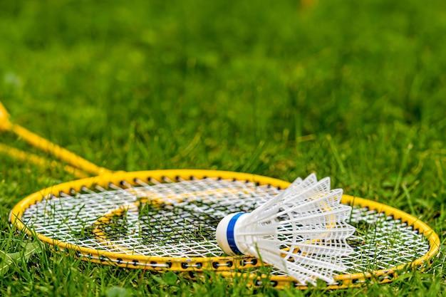 Witte shuttle op gele badmintonrackets in de groene weide
