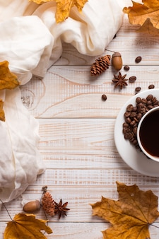 Witte sjaal, een kopje koffie met verspreide koffiebonen, droge gele bladeren op een houten tafel. herfststemming, copyspace.