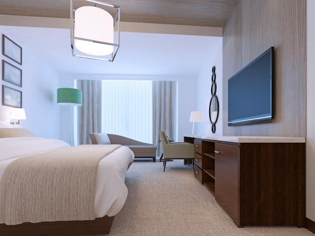 Witte slaapkamer met decoratieve nis van licht zebrano hout en bruin meubilair met wit aanrechtblad met aangeklede beb met deken en vloertapijt.