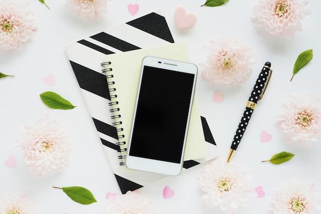 Witte smartphone met een zwart scherm op geel en zwart en wit gestreepte notitieboekjes, een zwarte pen met stippen en veel roze bloemen van chrysanten en groene bladeren op een witte tafel.