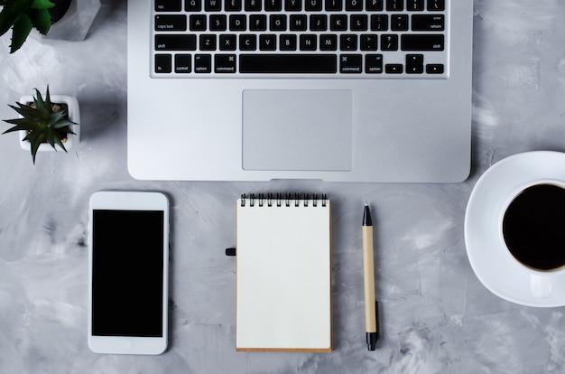 Witte smartphone met zwart leeg scherm op bureau met laptop en kopje koffie. bespotten van telefoon.