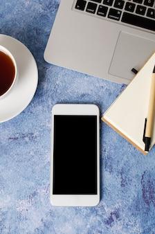 Witte smartphone met zwart leeg scherm op kantoor bureau met laptop, lege notebook en kopje thee. bespotten van telefoon.
