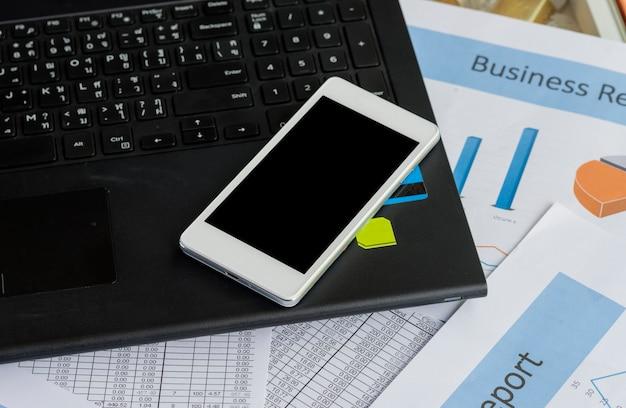 Witte smartphone met zwarte spatie op notitieboekje dichtbij bedrijfsgrafiekrapport bedrijfs concept.