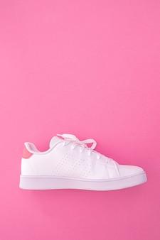 Witte sneaker op gekleurde achtergrond met kopie ruimte