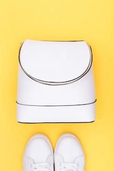 Witte sneakers en witte rugzak op geel