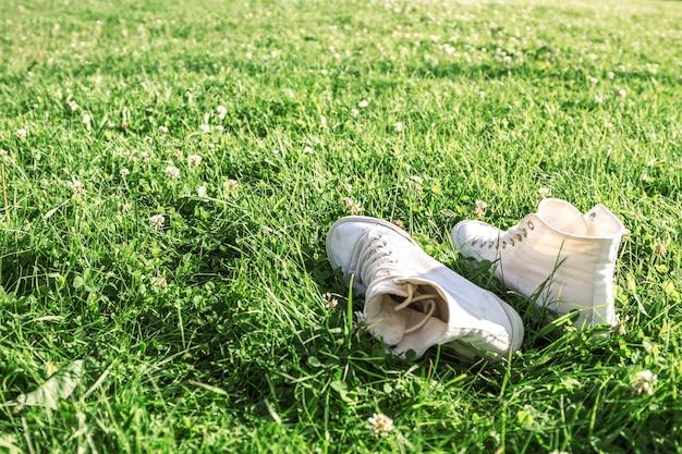 Witte sneakers gumshoes op een zomergras.
