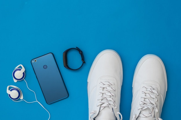 Witte sneakers, koptelefoon, slimme armband en blauwe smartphone op blauwe achtergrond. sportieve stijl. plat leggen. het uitzicht vanaf de top.