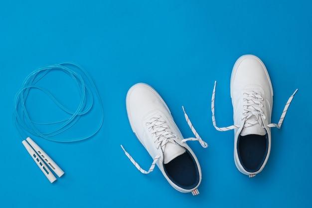 Witte sneakers met een blauw springtouw op blauw