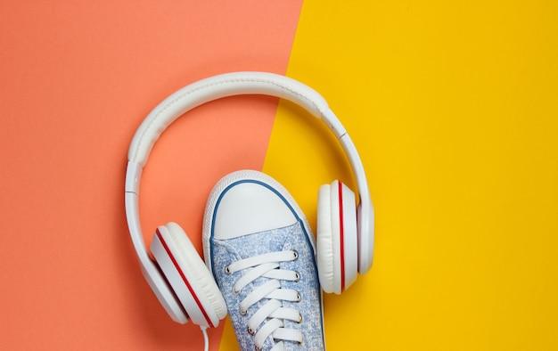 Witte sneakers met koptelefoon op gekleurde achtergrond. muziek concept. plat leggen, minimaal.