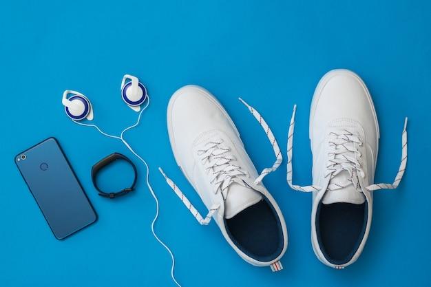 Witte sneakers met ongebonden veters, smartphone, koptelefoon en slimme armband op blauw oppervlak