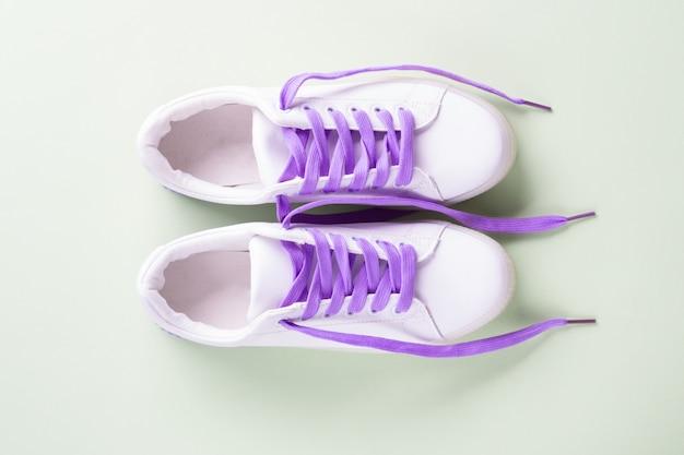Witte sneakers met paarse veters op groen