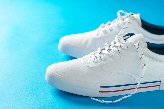 Witte sneakers met strepen op de zool op blauw