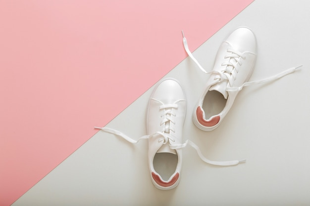 Witte sneakers met vliegende veters, vrouwelijke witte leren schoenen met veters op roze achtergrond. paar stijlvolle sneakers comfortabele sportkleding hipster damesschoenen. bovenaanzicht met kopie ruimte.
