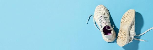 Witte sneakers onder ochtendzon op een blauwe achtergrond.