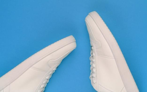 Witte sneakers op blauwe achtergrond. jeugd hipster concept. bovenaanzicht