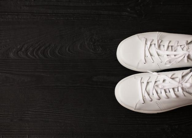 Witte sneakers op donkere houten achtergrond