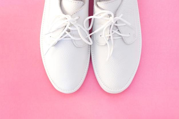 Witte sneakers op een roze achtergrond. uitzicht van boven. copyspace. plaats voor tekst