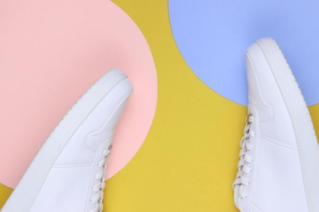 Witte sneakers op gele achtergrond met blauwe en roze pastelcirkels voor kopieerruimte. jeugd hipster concept. bovenaanzicht