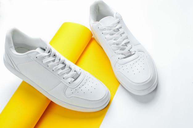 Witte sneakers op opgerolde rol geel papier. minimalistische mode