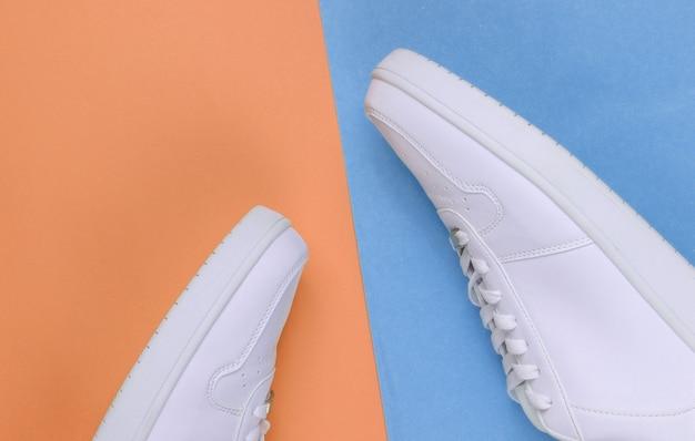 Witte sneakers op roze blauwe neonachtergrond. jeugd hipster concept. bovenaanzicht