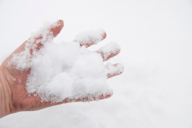 Witte sneeuw in de palm van je hand en op je vingers
