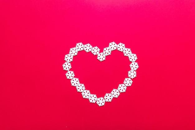 Witte sneeuwvlokdecoraties in de vorm van hart op rode achtergrond